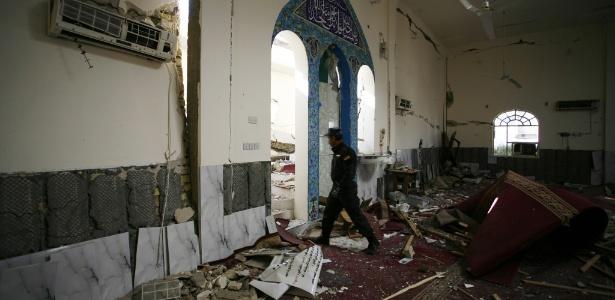 Policial iraquiano caminha pela mesquita sunita Ammar bin Yasser, em Hilla, atacada durante a noite