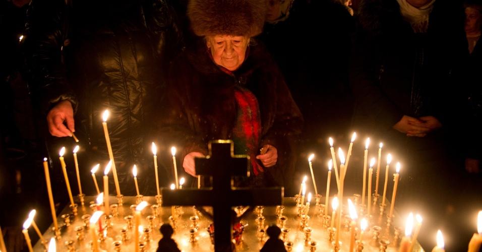 7.jan.2016 - Russa acende vela durante missa de Natal em igreja ortodoxa de Moscou. A Igreja Ortodoxa segue até hoje o calendário juliano, que antecedeu o calendário gregoriano - utilizado pela grande maioria da nações - e pelas diferenças de data, o Natal é celebrado com atraso na Rússia