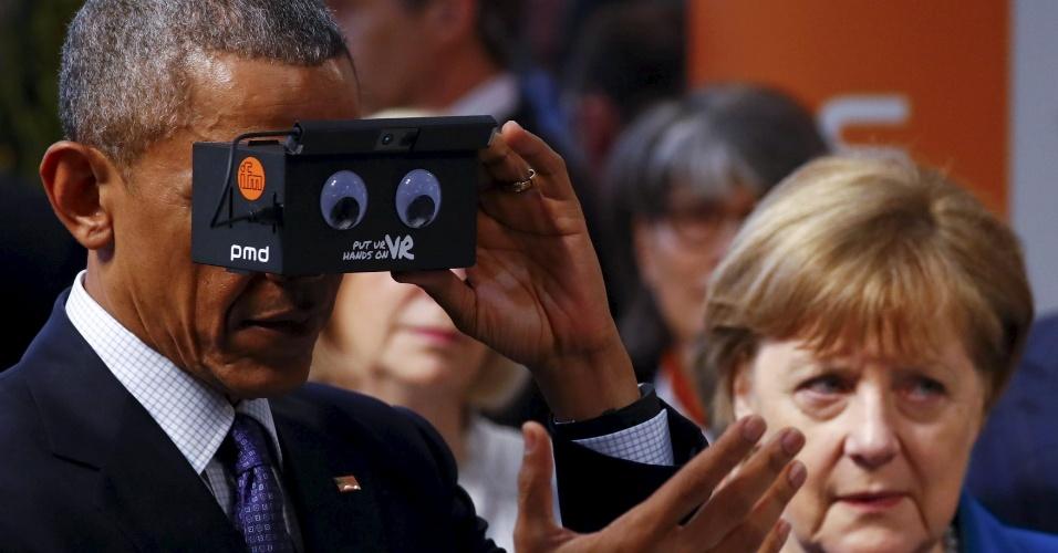 25.abr.2016 - O presidente norte-americano, Barack Obama, testa aparelho de realidade virtual ao lado da chanceler alemã, Angela Merkel, durante a abertura de feira de inovação em Hanover, na Alemanha