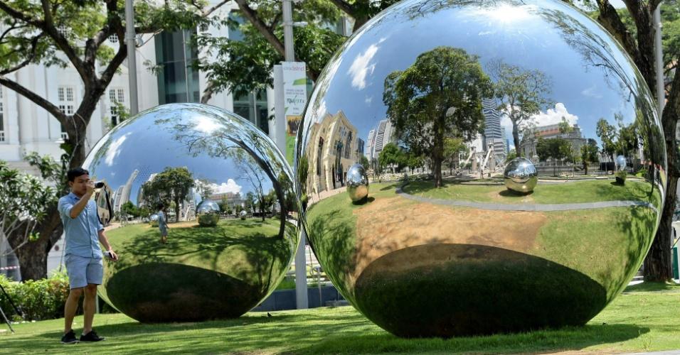 2.jun.2016 - Visitante fotografa obra composta de bolas de metal reflexivo, exibida nos jardins do Museu da Civilização Asiática, em Cingapura