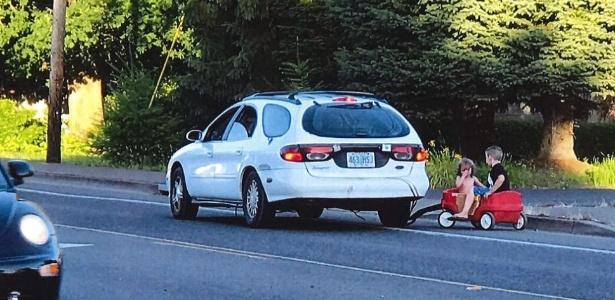Mulher usa seu carro para puxar os dois filhos que brincavam em carrinho infantil