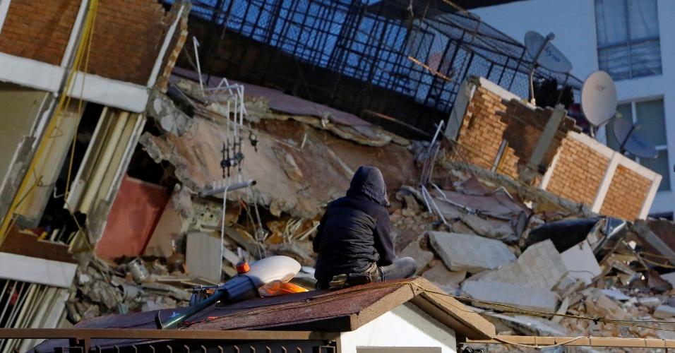 20.set.2017 - Homem senta em telhado de casa enquanto observa destroços de construção destruída após terremoto de magnitude 7,1 atingir a Cidade do México