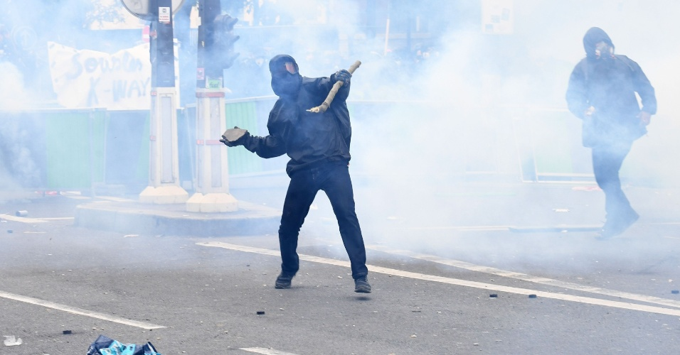 1.mai.2018 em Paris - França: Manifestante arremessa pedra durante manifestações. Prefeitura de Paris acionou polícia para conter 1.200 manifestantes encapuzados