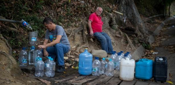 Com torneiras secas, pessoas buscam água em bica ao lado de estrada em Caracas