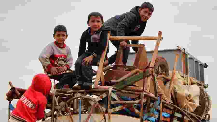 15.fev.2020 - Crianças se equilibram em cima de um caminhão-pipa cheio de objetos, no vilarejo rural Saharah, entre as províncias de Aleppo e Idlib, enquanto pessoas fogem dessas regiões, afetadas por ações militares do governo da Síria - Ibrahim Yasouf/AFP