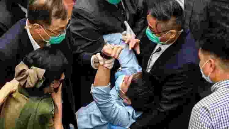 Parlamentar é detido por guardas no Conselho Legislativo de Hong Kong durante um conflito sobre um PL - Getty Images - Getty Images