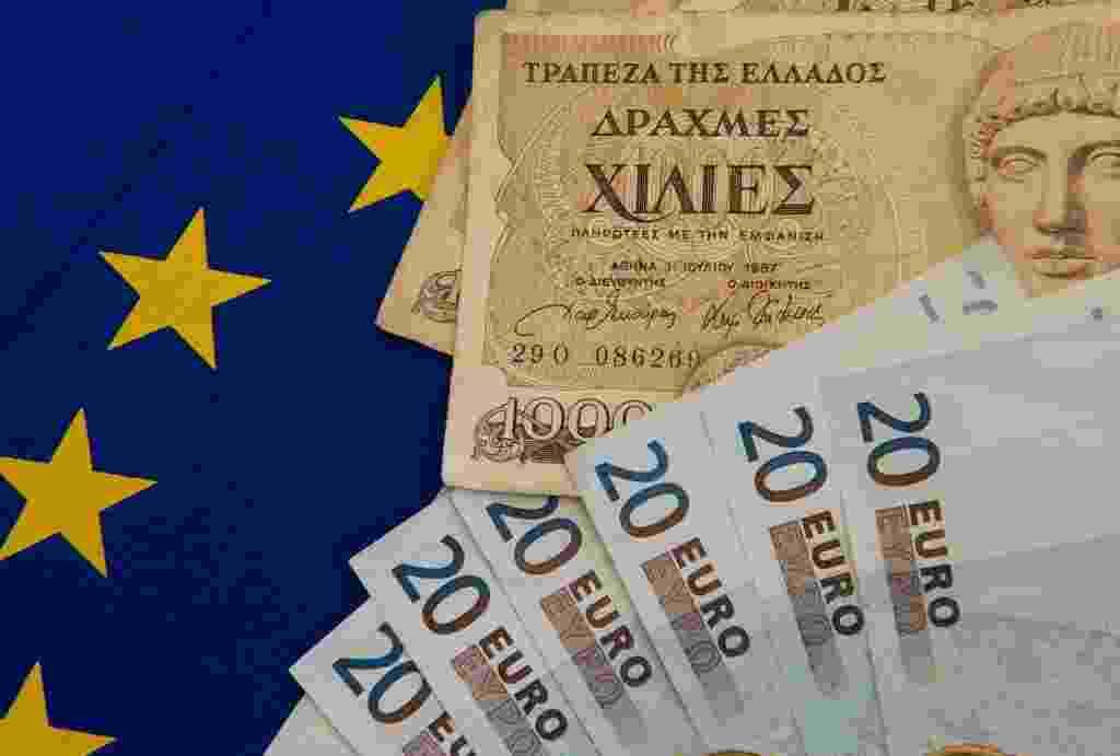 Notas de dracma (antiga moeda grega) junto a notas de euros e a bandeira da zona do euro; crise Grécia - Denis Charlet/AFP