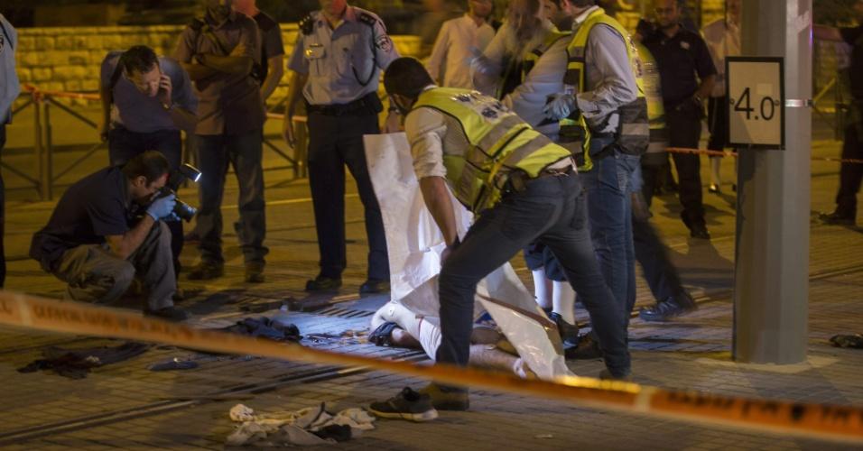 4.out.2015 - Policiais israelenses inspecionam o corpo de um palestino morto a tiros por forças de Israel após esfaquear um judeu de 15 anos em frente ao portão de Damasco, na cidade velha de Jerusalém, na madrugada deste domingo. É o segundo caso semelhante em menos de 24 horas. Na tarde deste sábado, um palestino matou dois judeus antes de ser morto por policiais, também na cidade velha de Jerusalém