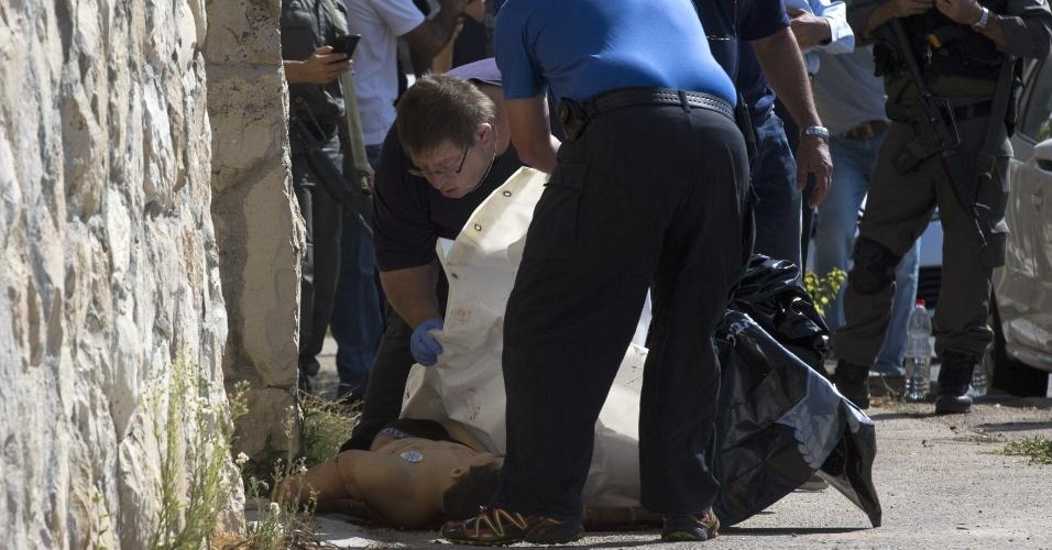 17.out.2015 - Funcionários de funerária cobrem o corpo de um palestino de 16 anos de idade morto em Jerusalém Oriental pela polícia israelense após esfaquear um oficial israelense que o deteve para um controle de identidade. Foi segundo ataque nesta manhã; em Hebron, na Cisjordânia, outro palestino foi morto após atacar um colono judeu, em mais um episódio de violência na região