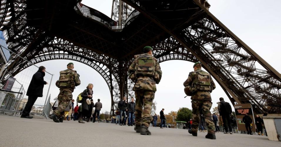 14.nov.2015 - Soldados franceses patrulham a torre Eiffel depois que ataques terroristas mataram dezenas de pessoas em Paris na véspera