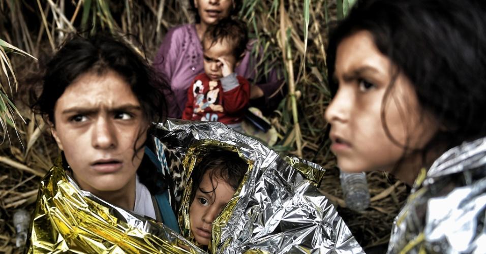 """28.set.2015 - Refugiados sírios protegidos com """"cobertores de vida"""" ao chegarem à ilha de Lesbos, depois de atravessar o mar Egeu da Turquia para a Grécia"""