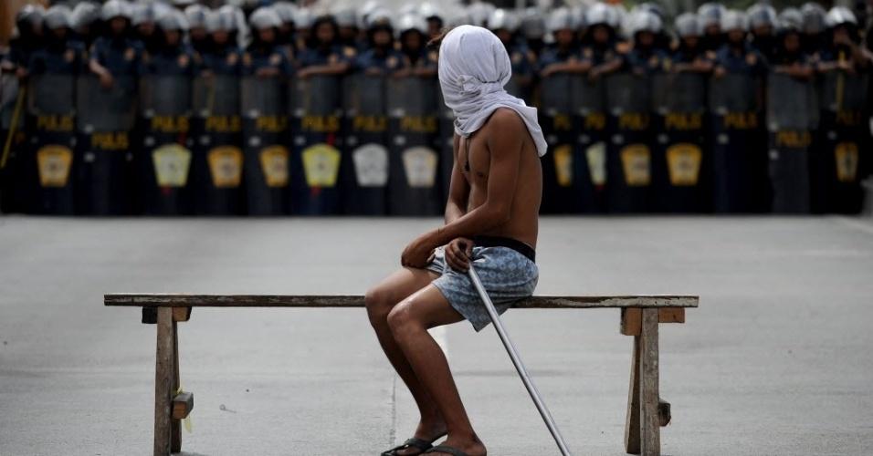 9.mar.2016 - Morador resiste sentado em banco à chegada de força policial em ação para demolição de barracos em Manila, nas Filipinas
