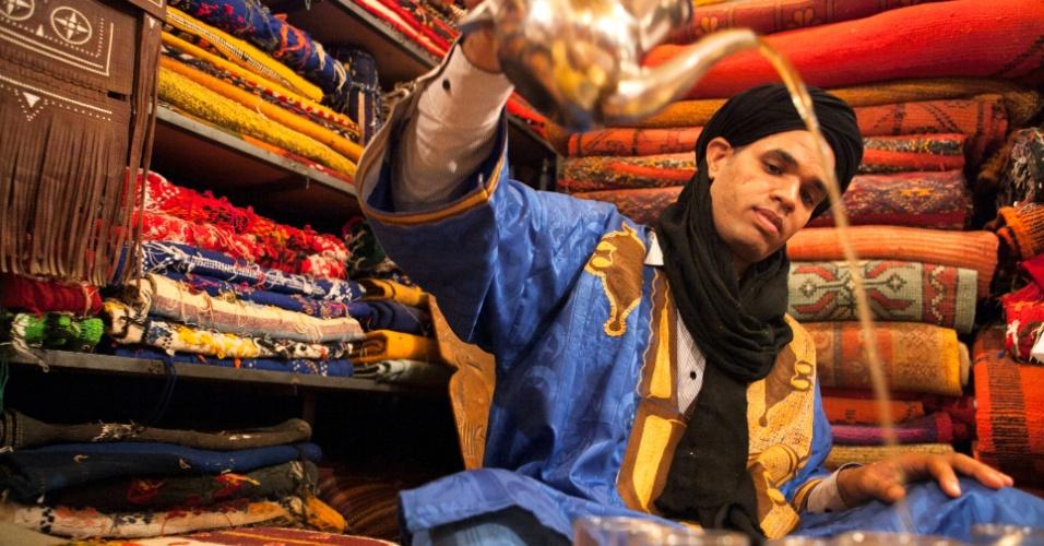 15.jun.2016 - Um homem numa aldeia berbere, vestido com roupas tradicionais, enche copos de chá numa loja marroquina de tapetes. O chá berbere é embalado com ervas frescas e oferecido em sinal de hospitalidade