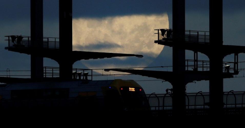 14.nov.2016 - Trem passa em ferrovia no subúrbio de Sydney com a superlua ao fundo
