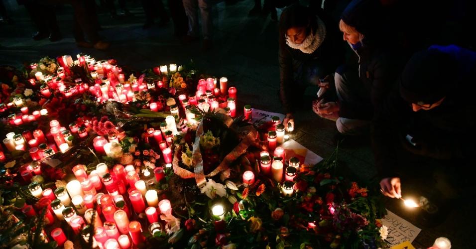20.dez.2016 - Pessoas acendem velas em um memorial improvisado em frente à igreja Memorial do Imperador Guilherme em Berlim, onde um caminhão invadiu um mercado natalino e matou ao menos 12 pessoas na segunda-feira (19)