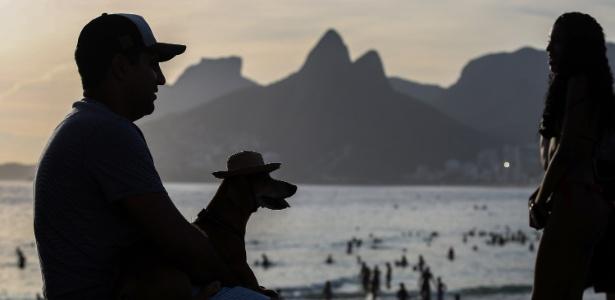 """27.dez.2016 - Com um cachorro """"vestindo"""" um chapéu personalizado no colo, homem observa a praia de Ipanema, na zona sul do Rio de Janeiro, pouco após o pôr do sol"""