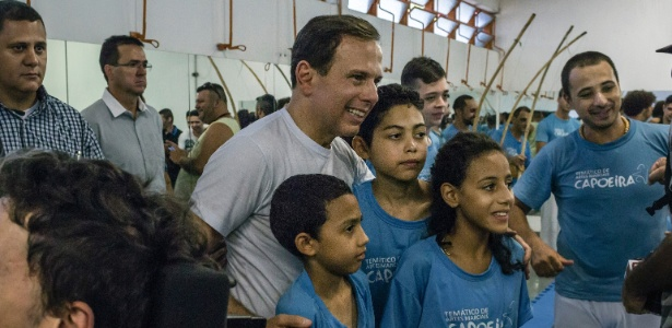 O prefeito João Doria (PSDB) posa para foto com crianças durante evento na Vila Carrão