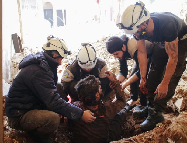 Capacetes brancos removem vítima de cratera após ter casa bombardeada em Daraa