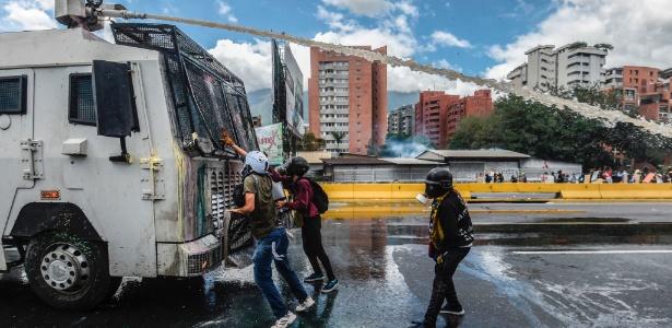 Manifestantes param diante de carro da polícia antidistúrbio durante protesto contra o governo Maduro em Caracas