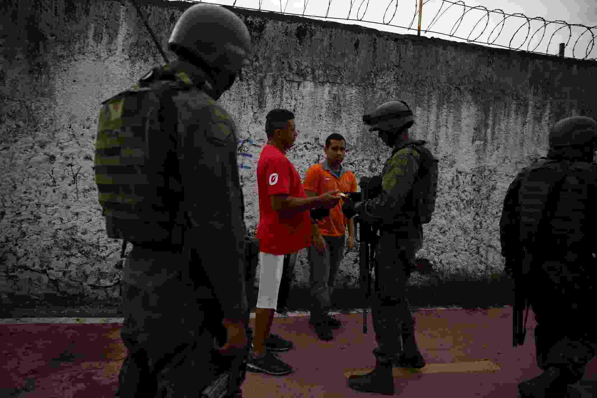 20.fev.2018 - Moradores da favela Kelson's, na zona norte do Rio de Janeiro, passam por ponto de inspeção das Forças Armadas. As entradas da comunidade foram ocupadas pelos militares do Exército. Ao menos quatro suspeitos foram presos até o final da manhã - Pilar Olivares/Reuters