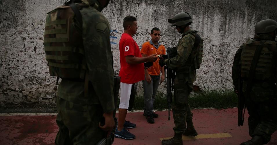 20.fev.2018 - Moradores da favela Kelson's, na zona norte do Rio de Janeiro, passam por ponto de inspeção das Forças Armadas. As entradas da comunidade foram ocupadas pelos militares do Exército. Ao menos quatro suspeitos foram presos até o final da manhã