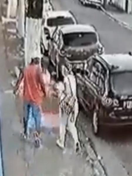 Imagem de câmera de segurança mostra vítima acompanhada de agressor instantes antes de ter o corpo queimado por ele com substância inflamável. Mulher está internada em estado grave e homem segue foragido - Reprodução/TV Globo