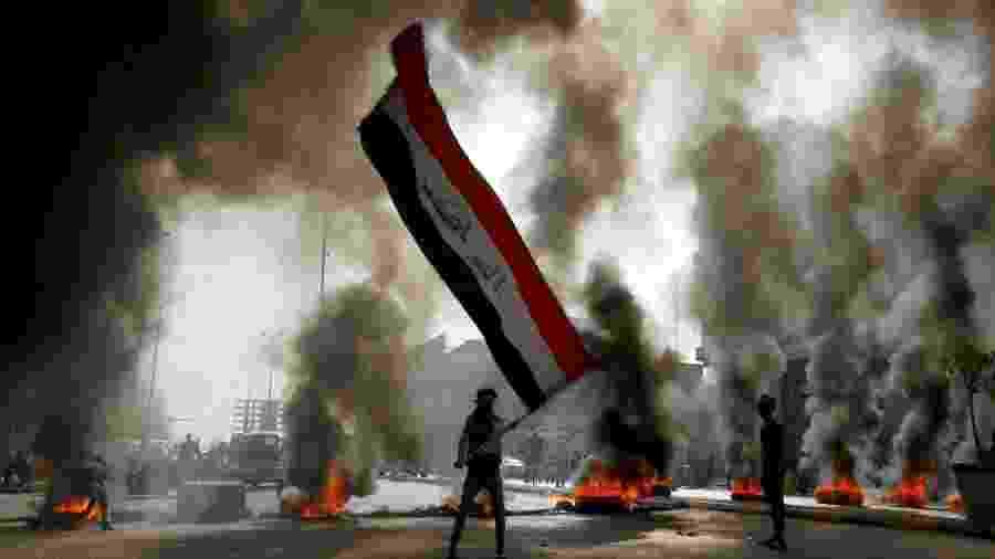 Manifestantes com a bandeira do Iraque, em Najaf, durante dia de protestos no país - Alaa al-Marjani/Reuters