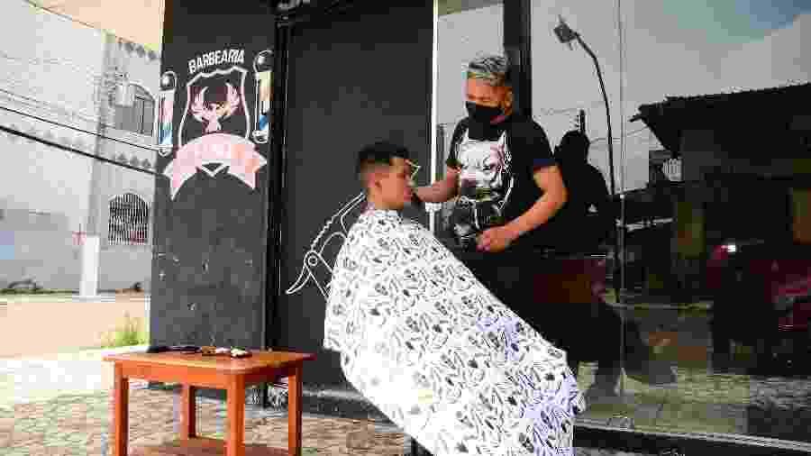 19.nov.2020 - Cabeleireiro corta cabelo na calçada devido à falta de energia elétrica em Macapá (AP). A falta de energia está causando diversos prejuízos aos moradores do estado desde o início do mês - ERICH MACIAS RODRIGUES/FUTURA PRESS/ESTADÃO CONTEÚDO