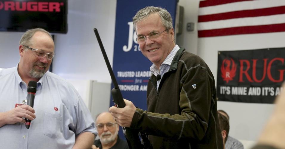 21.jan.2016 - Candidato republicano à Presidência dos EUA, Jeb Bush, sorri enquanto segura uma arma durante evento em Newport, New Hampshire (EUA)