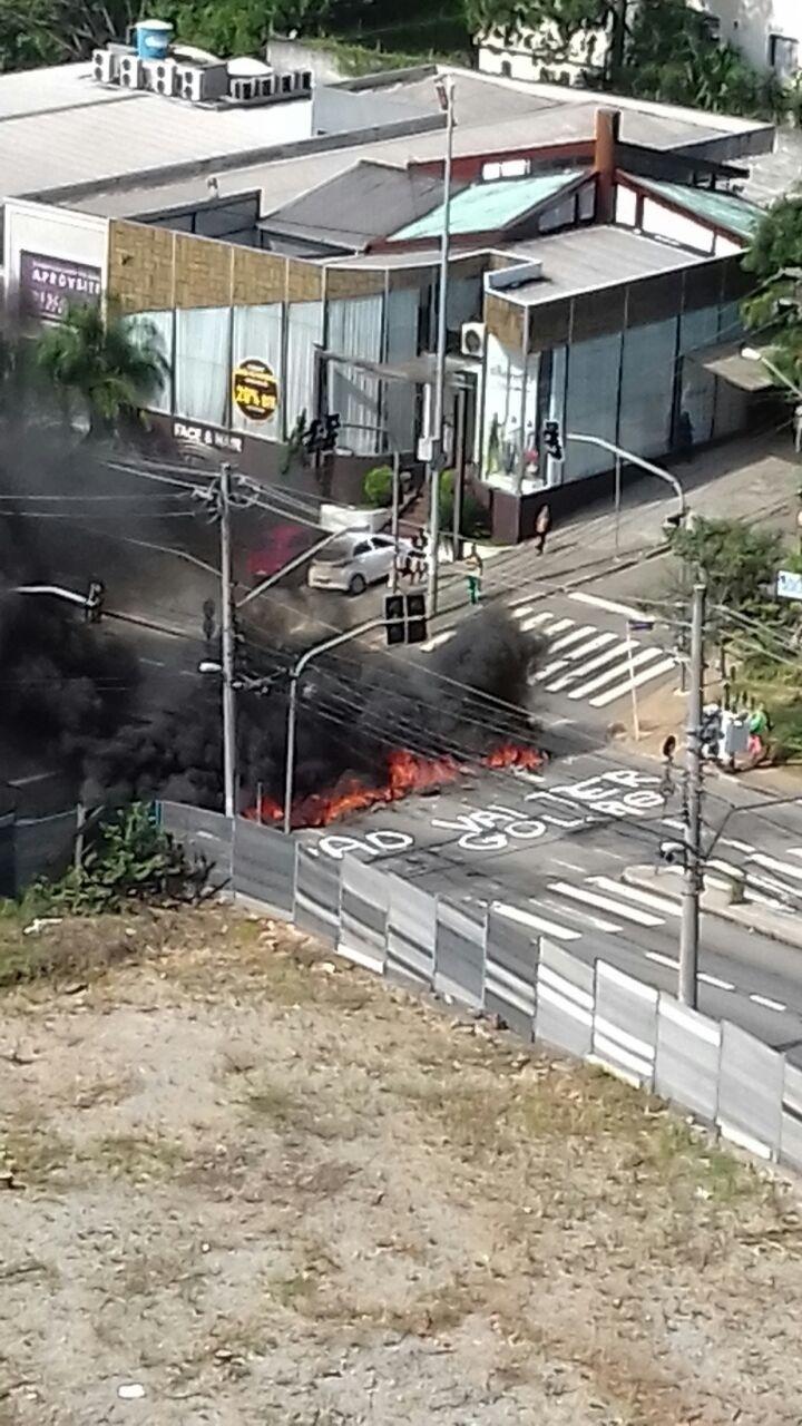 17.mar.2016 - Manifestantes colocam fogo em pneus, fecham cruzamento e picham a frase