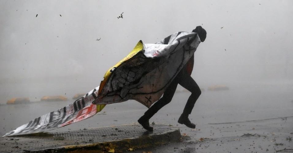5.mai.2016 - Um estudante corre segurando uma faixa para fugir da polícia durante uma manifestação para exigir mudanças no sistema de educação em Santiago, no Chile