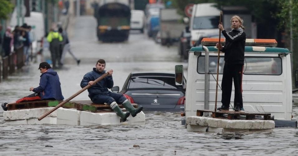 3.jun.2016 - Moradores que se recusaram a evacuar área alagada em Villeneuve-Trillage, no subúrbio de Paris, improvisam barcos para se deslocarem por ruas após fortes chuvas