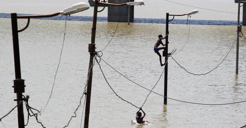 21.ago.2016 - Meninos escalam postes para fugir de enchente do rio Ganga, em Allahabad, na Índia