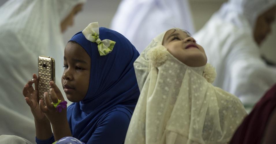 12.set.2016 - Menina olha o telefone celular dentro da sala de oração, durante reza no dia de celebrações Eid al-Adha na Mesquita Haroon em Bancoc, na Tailândia