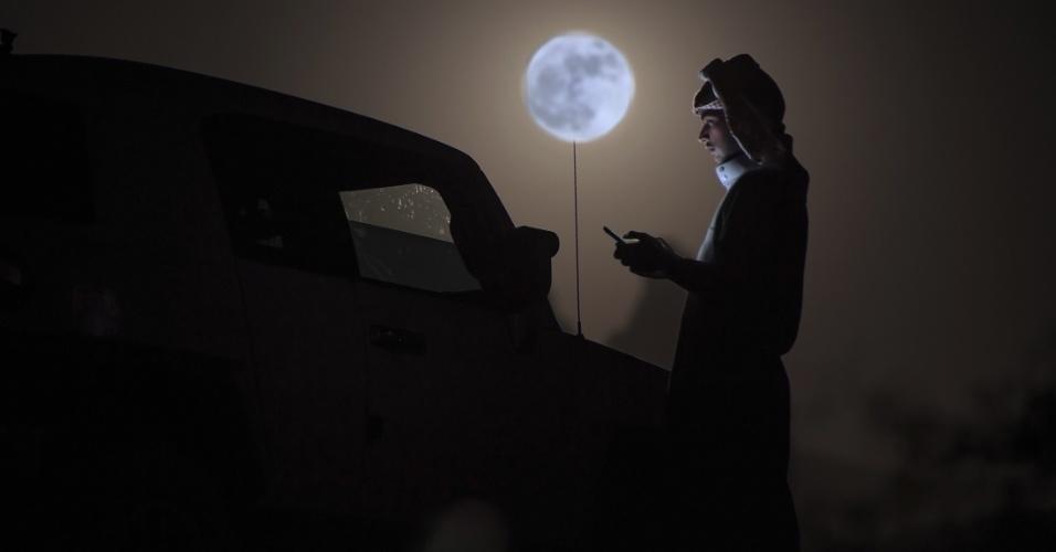 Homem verifica o celular sob o luar da superlua no deserto perto de Tabuk, na Arábia Saudita