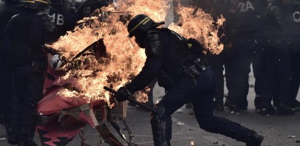 Manifestantes lançam carrinho de supermercado em chamas contra policiais durante ato pelo 1º de Maio em Paris, França