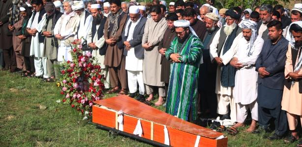 Parentes, amigos e colegas rezam ao lado do caixão do fotógrafo da agência AFP, Shah Marai, morto no atentado