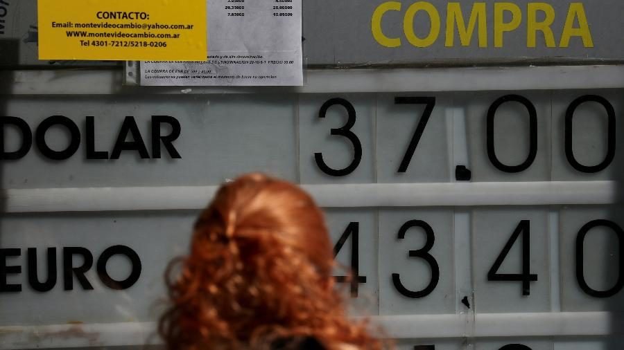 Mulher olha para placa de câmbio em Buenos Aires, na Argentina - Marcos Brindicci/Reuters