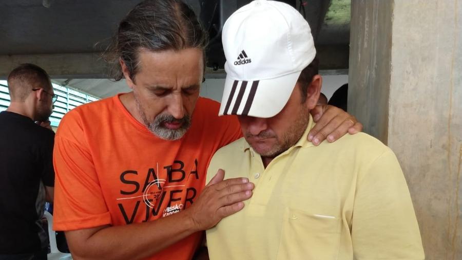 O pedreiro Wilson Joaquim da Fonseca Silva (de boné), amparado por um voluntário na Estação Conhecimento - Luciana Quierati/UOL