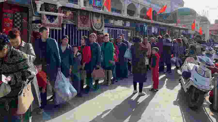 Consumidores fazem fila para verificação de documentos nos arredores do mercado de Kashgar na região de Xinjiang, na China - Paul Mozur/The New York Times