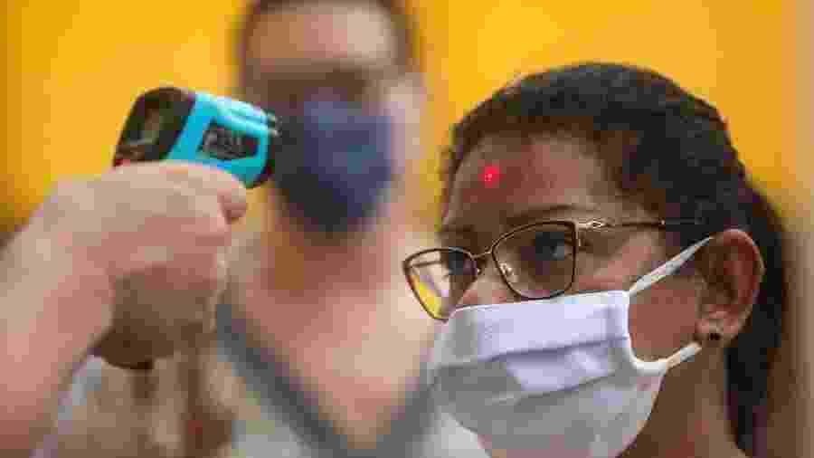 10.jun.2020 - Mulher tem a temperatura corporal medida na rua 25 de Março, em São Paulo - Werther Santana/Estadão Conteúdo