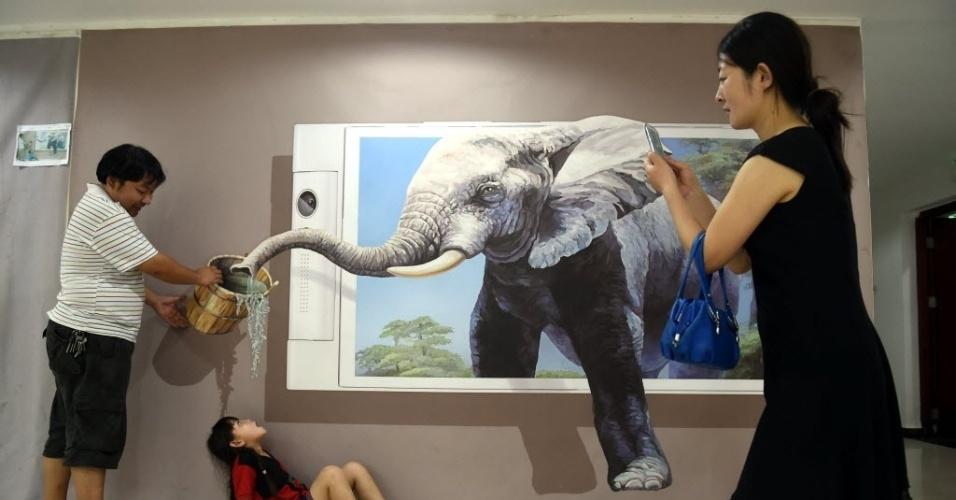 25.ago.2015 - Menina posa durante exposição de pinturas em 3D na província de Hebei, China
