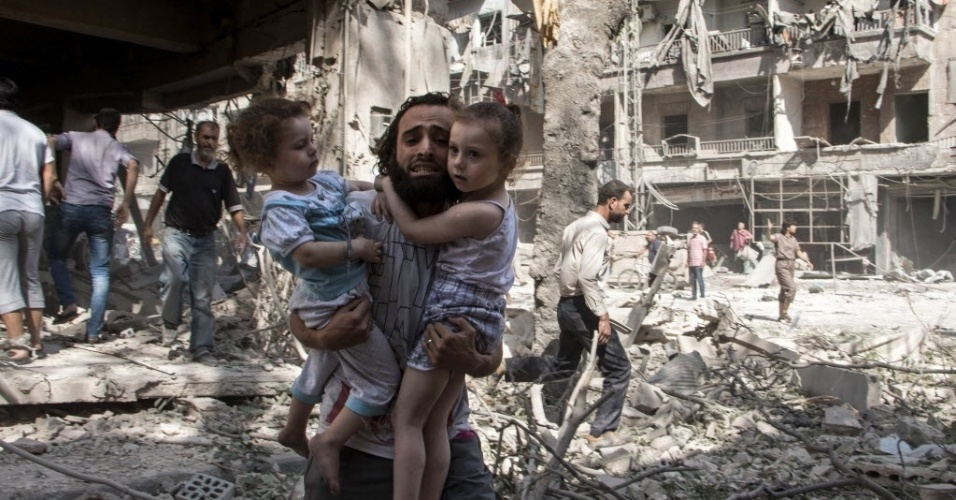 17.set.2015 - Sírio carrega duas crianças enquanto caminha pelos escombros após um ataque do governo sírio no bairro de al-Kalasa, ao norte da cidade síria de Aleppo. Pelo menos 25 civis morreram