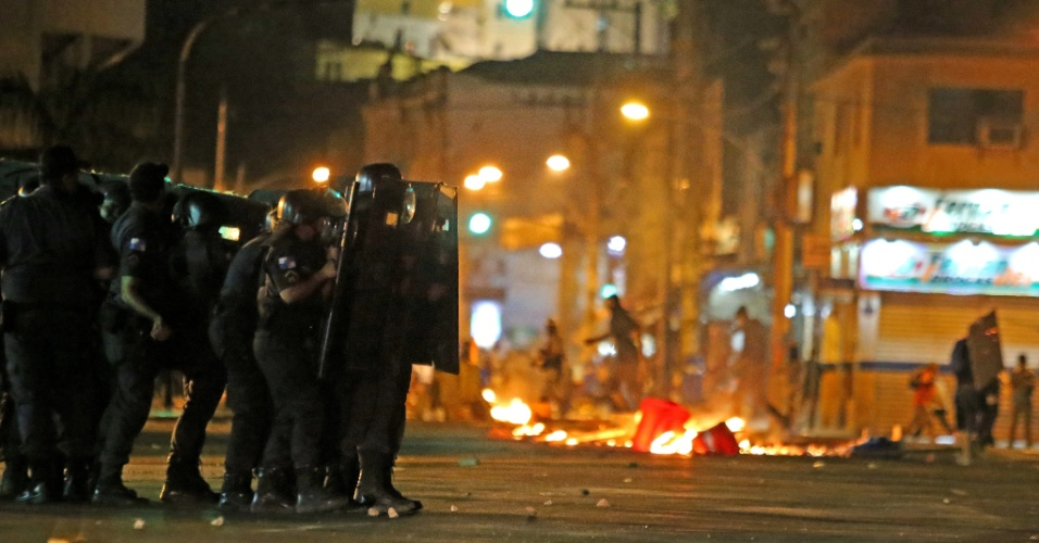 8.jan.2016 - Policiais formam barreira em frente a barricada de lixo durante confusão em ato contra o aumento das passagens de ônibus, em à Central do Brasil, no centro do Rio de Janeiro. O valor passou de R$ 3,40 para R$ 3,80 no último dia 2