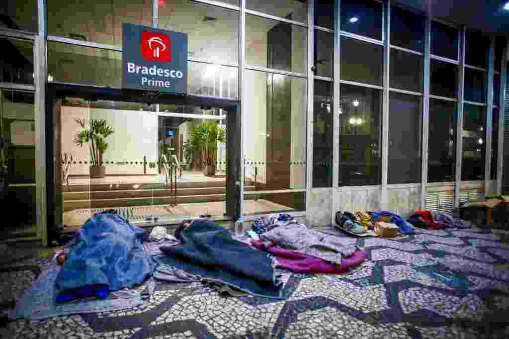 14.jun.2016 - Moradores de rua dormem em calçada em São Paulo. Quem encontrar uma pessoa precisando de ajuda pode ligar para a Central de Atendimento Permanente e de Emergência da Prefeitura, que funciona 24 horas por dia. O telefone é 156. Equipes da Secretaria de Assistência e Desenvolvimento Social vão convidar essas pessoas a irem para abrigos. A população também pode ajudar doando roupas, sapatos, agasalhos e cobertores. Há diversos pontos de coleta espalhados pela cidade. No site da Campanha do Agasalho do governo estadual é possível descobrir o local mais próximo digitando o CEP da residência - Edson Lopes Jr./UOL