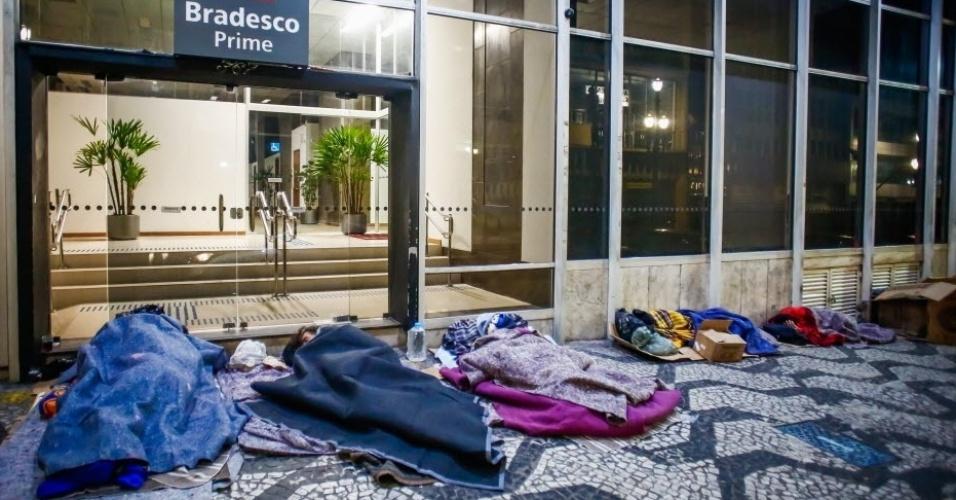 14.jun.2016 - Moradores de rua dormem em calçada em São Paulo. Quem encontrar uma pessoa precisando de ajuda pode ligar para a Central de Atendimento Permanente e de Emergência da Prefeitura, que funciona 24 horas por dia. O telefone é 156. Equipes da Secretaria de Assistência e Desenvolvimento Social vão convidar essas pessoas a irem para abrigos. A população também pode ajudar doando roupas, sapatos, agasalhos e cobertores. Há diversos pontos de coleta espalhados pela cidade. No site da Campanha do Agasalho do governo estadual é possível descobrir o local mais próximo digitando o CEP da residência