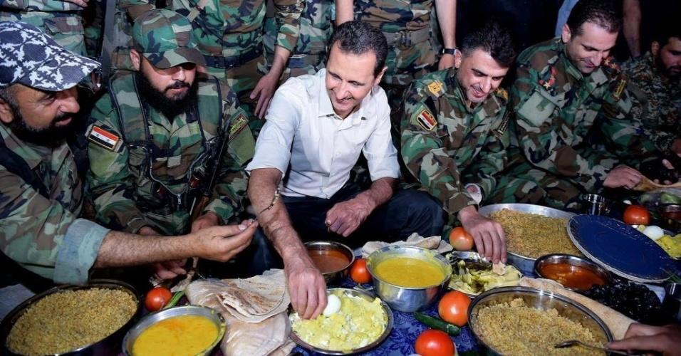 26.jun.2016 - O presidente sírio, Bashar al-Assad (ao centro), postou em sua página no Facebook uma foto de um jantar com soldados sírios na região de al-Marj, na província de Damasco, para celebrar o Ramadã, mês sagrado para os muçulmanos