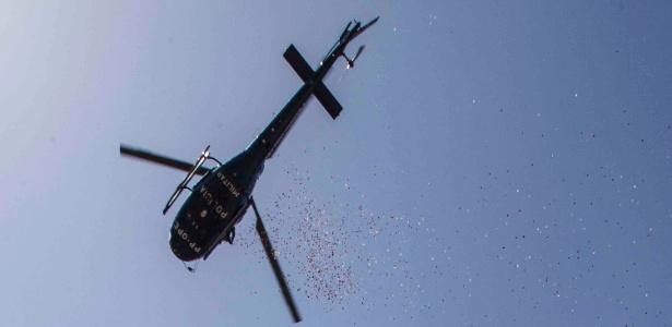 Pétalas de rosas são jogadas de helicóptero que sobrevoa o velório