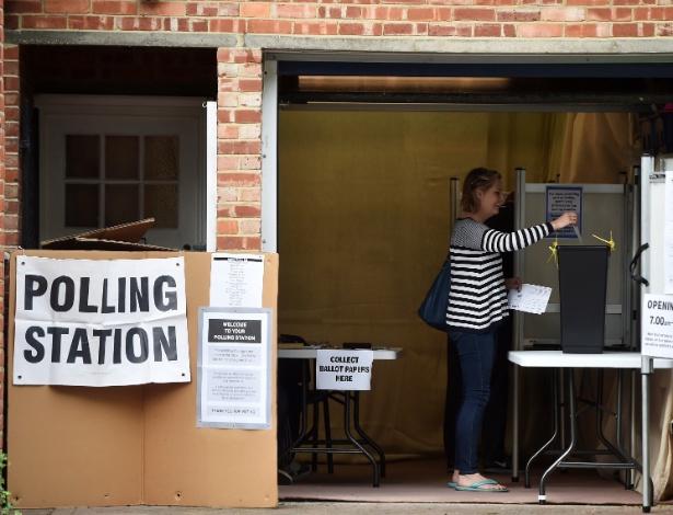 Mulher deposita voto em garagem usada como sessão de votação na Grande Londres