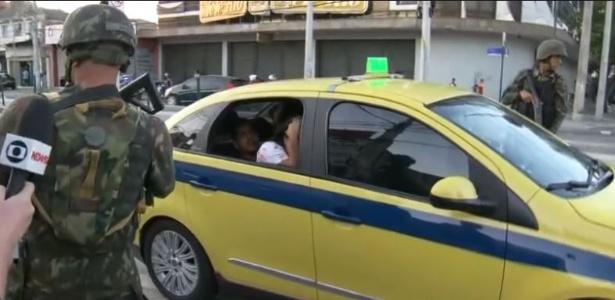 Imagem da Rede Globo mostra suspeito tentando escapar de cerco militar em taxi - Reprodução/Rede Globo